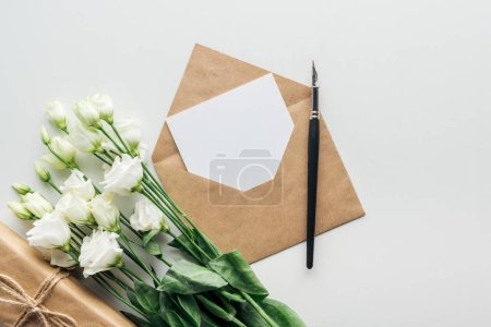 Photo for Top view of eustoma, wrapped gift, envelope with empty card and ink pen on grey background - Royalty Free Image