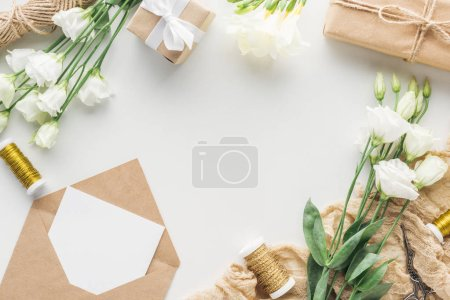 Photo for Top view of flowers, wrapped gifts, envelope with empty card and cloth on grey background - Royalty Free Image