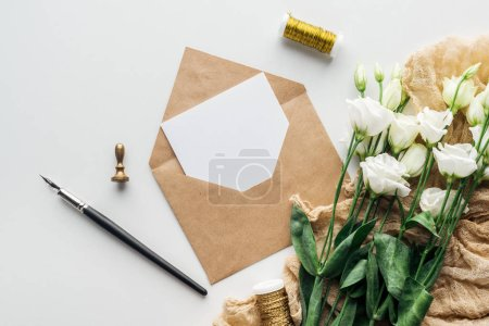 Photo for Top view of eustoma, envelope with empty card, cloth and ink pen on grey background - Royalty Free Image