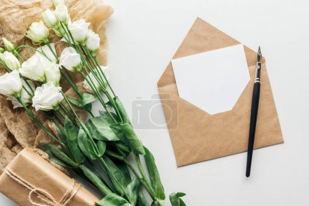 Photo for Top view of eustoma, envelope with empty card, wrapped gift, cloth and ink pen on grey background - Royalty Free Image