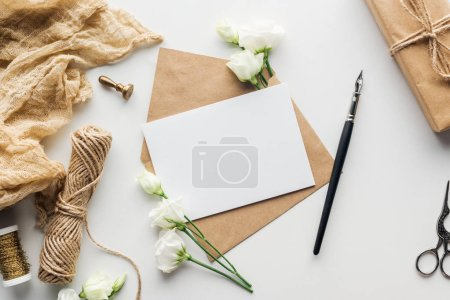 Photo for Top view of flowers, cloth, stamp, envelope with empty card and ink pen on grey background - Royalty Free Image