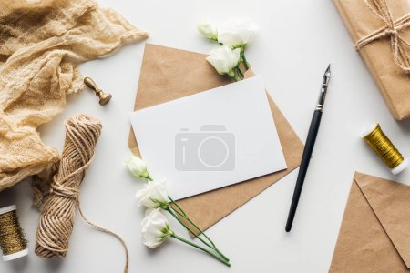 Photo for Top view of eustoma, cloth, stamp, envelope with empty card and ink pen on grey background - Royalty Free Image