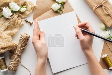 Photo for Cropped view of woman writing in card with ink pen over eustoma, cloth, envelope and wrapped gift on grey background - Royalty Free Image