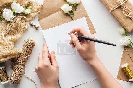 Photo pour Vue recadrée de femme écrivant en carte avec stylo à encre près des fleurs, tissu, enveloppe et cadeau enveloppé sur fond gris - image libre de droit