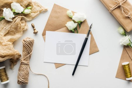 Photo for Top view of envelope with empty card and ink pen, flowers, cloth, stamp, wrapped gift on grey background - Royalty Free Image