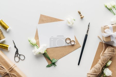 Foto de Vista superior sobre con tarjeta vacía, pluma de tinta, flores, sello, regalos envueltos, tijeras, hilo y anillos de boda oro en fondo gris - Imagen libre de derechos