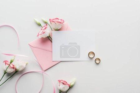 Foto de Vista superior de la tarjeta vacía con sobre color de rosa, flores, cinta de seda y oro anillos de boda en fondo gris - Imagen libre de derechos