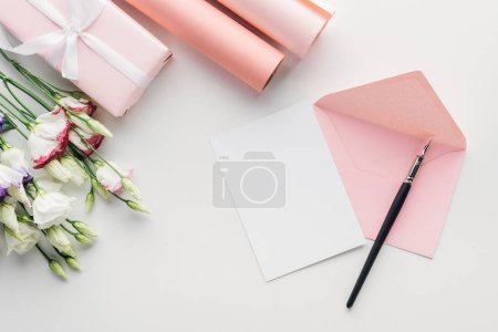 Photo for Top view of pink envelope with empty card and ink pen, flowers, wrapped gift, rolls of paper on grey background - Royalty Free Image