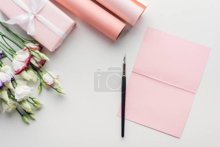 Photo for Top view of pink empty card with ink pen, flowers and rolls of paper on grey background - Royalty Free Image