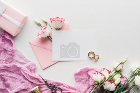 Photo for Top view of empty card with pink envelope, flowers, cloth, wrapped gift, scissors and golden wedding rings on white background - Royalty Free Image