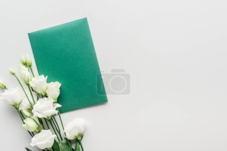 Photo for Top view of empty green envelope with flowers on grey background - Royalty Free Image