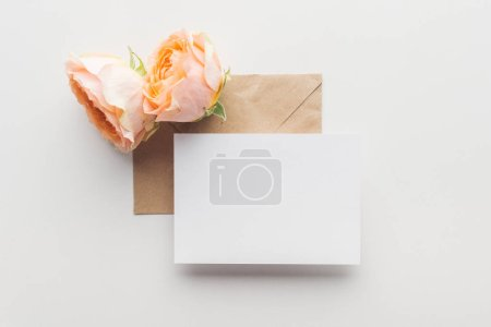 Photo for Top view of empty blank over brown envelope and pink roses on grey background - Royalty Free Image