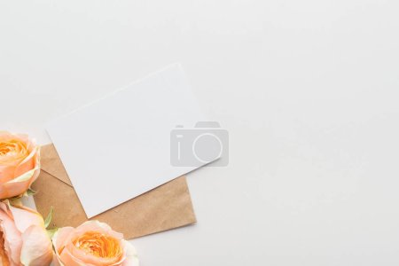 Photo for Top view of empty blank with brown envelope and pink roses on grey background - Royalty Free Image