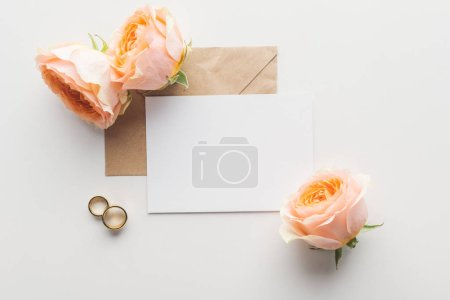 top view of empty card with brown craft paper envelope, roses and golden wedding rings on grey background