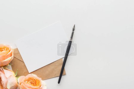 Photo for Top view of empty blank with brown envelope, ink pen and pink roses on grey background - Royalty Free Image