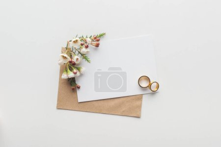 top view of empty card with brown craft paper envelope and wedding rings on grey background