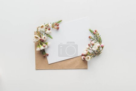 Photo for Top view of empty blank with brown envelope and flowers on grey background - Royalty Free Image