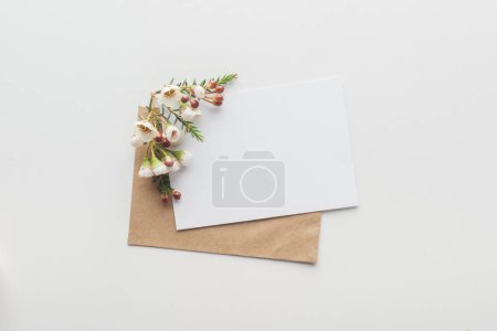Photo for Top view of empty blank with brown craft paper envelope and flowers on grey background - Royalty Free Image