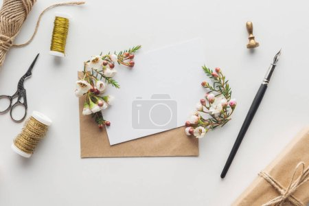 Photo for Top view of empty blank with brown envelope, ink pen, flowers, scissors, stamp, spools of thread and wrapped gift on grey background - Royalty Free Image