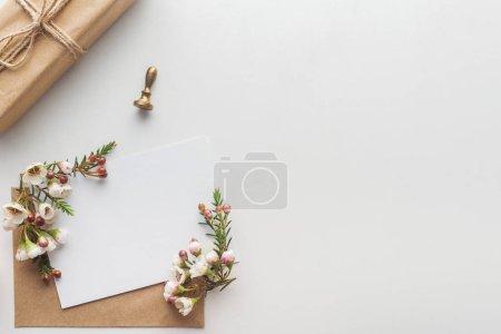 Foto de Vista superior del vacío en blanco con marrón sobre, flores, sellos y regalo envuelto en fondo gris - Imagen libre de derechos