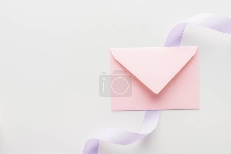 Photo for Top view of pink envelope and purple silk ribbon on grey background - Royalty Free Image