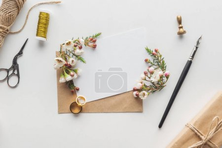 Photo for Top view of empty card with envelope, ink pen, flowers, wrapped gift, stamp, scissors, spool of thread and wedding rings on grey background - Royalty Free Image
