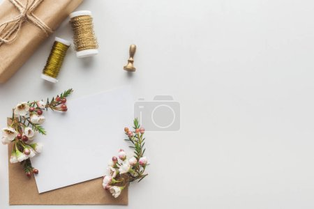 Photo for Top view of empty blank with brown envelope, flowers, stamp, wrapped gift and spools of thread on grey background - Royalty Free Image