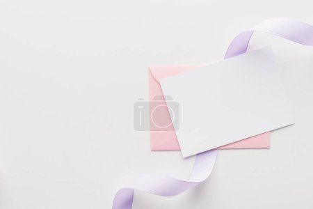 Photo for Top view of empty blank with pink envelope and purple silk ribbon on grey background - Royalty Free Image