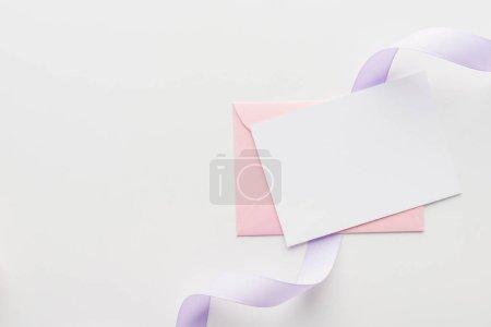 Photo pour Vue du dessus du blanc vide avec enveloppe rose et ruban de soie violet sur fond gris - image libre de droit