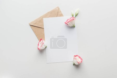 top view of empty blank with brown craft paper envelope and eustoma on grey background