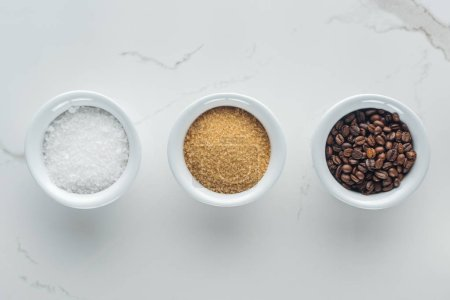 Photo for Top view of bowls with salt, coffee grains and brown sugar on white surface - Royalty Free Image