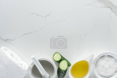 Photo for Top view of bowls with oil and salt, cucumber halves, pounder and towel on white surface - Royalty Free Image