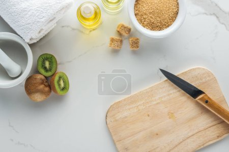 Photo for Top view of various natural ingredients for cosmetics making, and cutting desk with kiwi on white surface - Royalty Free Image