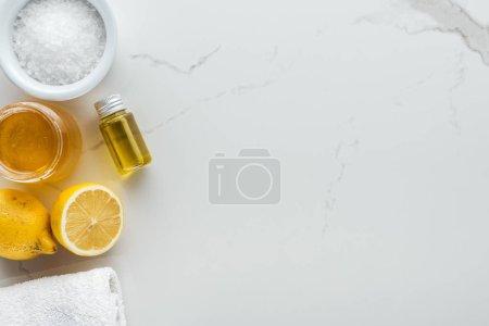 Foto de Vista superior de limones, miel, sal y otros ingredientes naturales para cosméticos hechos a mano sobre superficie blanca - Imagen libre de derechos
