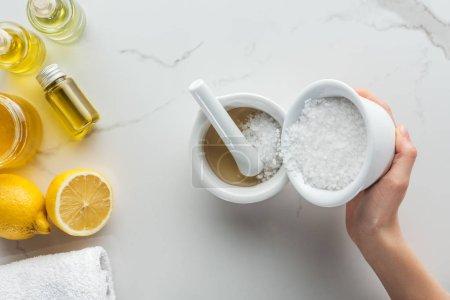 Foto de Vista parcial de verter sal en libras sobre la superficie blanca de mujer - Imagen libre de derechos