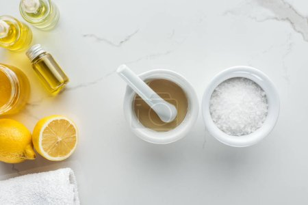 Photo for Top view of pounder, bowl with salt, and various natural components for homemade cosmetics on white surface - Royalty Free Image