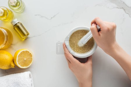 partial view of woman making salt and oil scrub in pounder on white surface