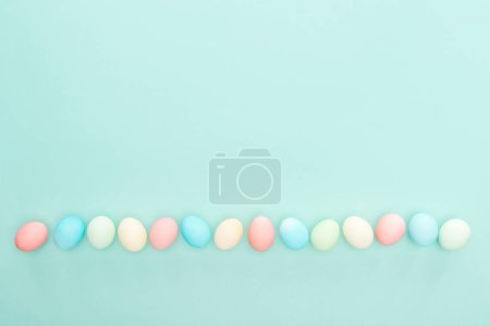Photo for Top view of traditional easter eggs in row isolated on blue - Royalty Free Image