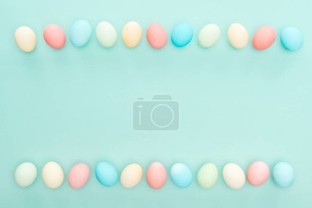 Photo for Top view of traditional pastel easter eggs in rows isolated on blue - Royalty Free Image