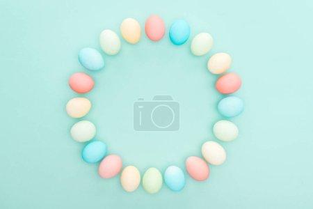 Photo pour Vue de dessus des pastels oeufs de Pâques comme cadre cercle isolée sur bleu - image libre de droit