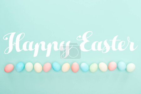Photo for Top view of pastel painted eggs in row with Happy easter lettering isolated on blue - Royalty Free Image