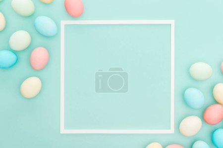 top view of traditional easter eggs near empty frame isolated on blue