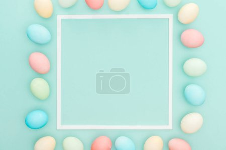 Photo for Top view of traditional pastel easter eggs near frame isolated on blue - Royalty Free Image