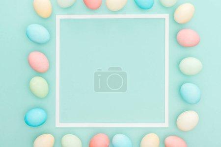 Photo pour Vue de dessus des traditionnels oeufs de Pâques pastel près cadre isolé sur bleu - image libre de droit