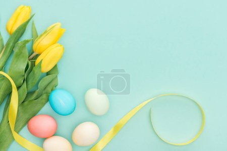Photo for Top view of yellow tulips with ribbon and easter eggs isolated on blue - Royalty Free Image
