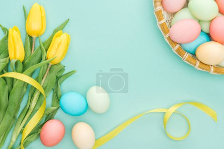 Photo for Top view of yellow tulips with ribbon and easter eggs in wicker plate isolated on blue - Royalty Free Image