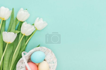 Photo for Top view of tulip flowers and easter eggs in wicker basket isolated on blue with copy space - Royalty Free Image