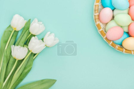 Photo for Top view of white tulips and easter eggs in wicker plate isolated on blue - Royalty Free Image