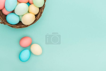 Photo for Top view of traditional pastel easter eggs in wicker basket isolated on blue with copy space - Royalty Free Image