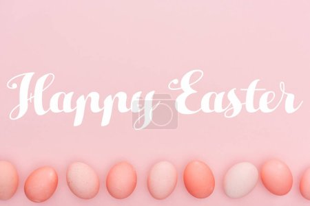 Photo for Happy Easter lettering with traditional painted eggs in row isolated on pink - Royalty Free Image